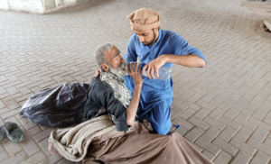 man helping a Syrian refugee by providing water